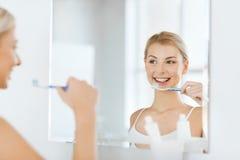 Женщина с зубами чистки зубной щетки на ванной комнате Стоковое Фото