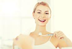 Женщина с зубами чистки зубной щетки на ванной комнате Стоковая Фотография RF