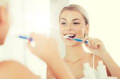 Женщина с зубами чистки зубной щетки на ванной комнате Стоковое Изображение