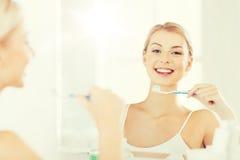 Женщина с зубами чистки зубной щетки на ванной комнате Стоковые Фото