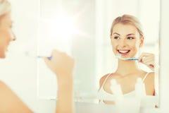 Женщина с зубами чистки зубной щетки на ванной комнате Стоковая Фотография