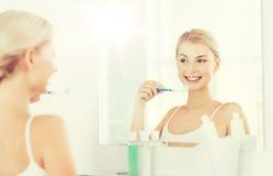 Женщина с зубами чистки зубной щетки на ванной комнате Стоковое фото RF