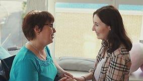 Женщина с инвалидностью в кресло-коляске говоря к ее дочери Медленный mo акции видеоматериалы