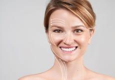Женщина с линиями массажа прикладывать политуру кожи внимательности прозрачную Обработка подтяжки лица против старения стоковые фотографии rf