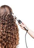 Женщина с длинными волосами, утюгами парикмахера руки завивая на белизне Стоковые Фотографии RF
