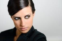 Женщина с интенсивным взглядом на белой предпосылке Стоковая Фотография