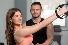 Женщина с личными ремнями фитнеса Trx поезда тренера стоковые фотографии rf
