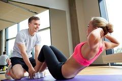 Женщина с личным тренером делать сидит поднимает в спортзале стоковые изображения rf