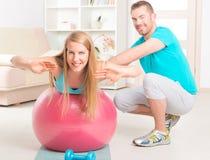 Женщина с личным тренером дома Стоковая Фотография RF