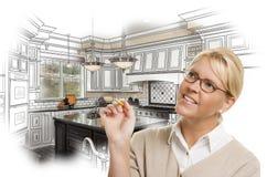Женщина с карандашем над изготовленными на заказ чертежом дизайна кухни и фото c стоковое изображение