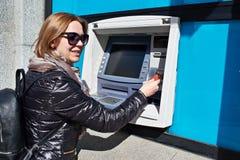 Женщина с карточкой банка на ATM Стоковое Фото