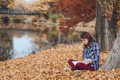 Женщина с книгой в парке осени Стоковое Изображение RF