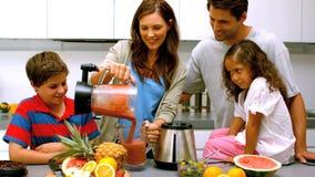 Женщина с коктеилем плодоовощ семьи лить от blender сток-видео