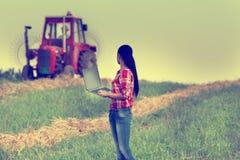 Женщина с компьтер-книжкой в поле Стоковые Изображения RF