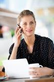 Женщина с компьтер-книжкой и телефоном стоковые изображения