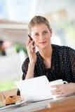 Женщина с компьтер-книжкой и телефоном стоковые фотографии rf