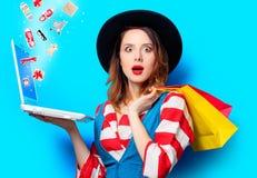 Женщина с компьтер-книжкой и хозяйственными сумками стоковые фото