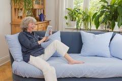 Женщина с компьтер-книжкой на софе Стоковое Изображение RF