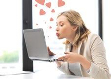 Женщина с компьютером целуя экран Стоковое фото RF