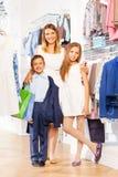 Женщина с концом стойки мальчика и девушки пока ходящ по магазинам Стоковая Фотография