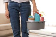 Женщина с корзиной профессиональных чистящих средств внутри помещени стоковые фото