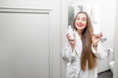 Женщина с косметиками в ванной комнате Стоковые Фото