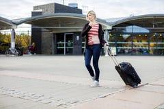 Женщина с, который катят багажом идя вне вокзала стоковые фотографии rf