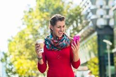 Женщина с кофе и телефоном в городе Стоковая Фотография