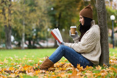 Женщина с кофе книги выпивая в парке осени Стоковое Изображение