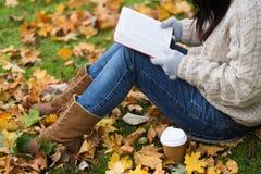 Женщина с кофе книги выпивая в парке осени Стоковое фото RF