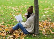 Женщина с кофе книги выпивая в парке осени Стоковые Фотографии RF