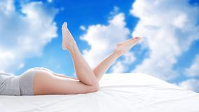 Женщина с красивыми ногами на запачканной предпосылке неба с облаками стоковые изображения rf
