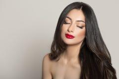 Женщина с красной губной помадой и темными толстыми волосами Закрытые глаза стоковые изображения