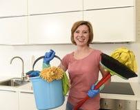 Женщина с красными волосами в перчатках резины моя держа mop и веник ведра чистки Стоковые Фото