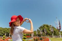 Женщина с красными цветками рамок шляпы в форму сердца, рамку сердца пальца смотреть и усмехаться к камере стоковые изображения