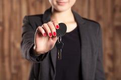 Женщина с красным лаком на ногтях держит ключи автомобиля на коричневой предпосылке Стоковое фото RF