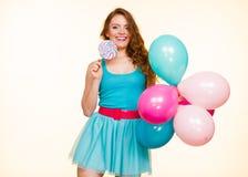 Женщина с красочными воздушными шарами и леденцом на палочке стоковое фото