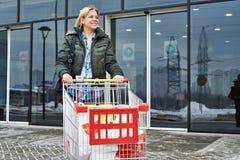 Женщина с магазинной тележкаой выходит магазин стоковое изображение rf