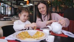 Женщина с меньшей дочерью в ресторане, ест только сваренную пиццу сыра Мать льет чай в чашку сток-видео