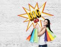 Женщина с множественными хозяйственными сумками около большого плаката продажи на br Стоковая Фотография