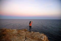 Женщина с мобильным телефоном на морском побережье на заходе солнца стоковые фото