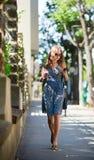 Женщина с мобильным телефоном в улице стоковые изображения