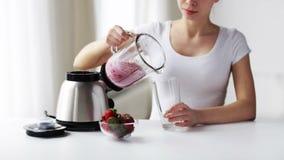 Женщина с молочным коктейлем опарника blender лить видеоматериал