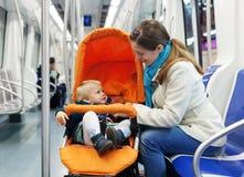 Женщина с младенцем в прогулочной коляске на метро Стоковое Фото