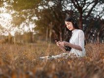 Женщина с наушниками слушая к музыке от умного телефона и si Стоковое Изображение RF