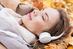 Женщина с наушниками слушая к музыке в осени Стоковое Фото