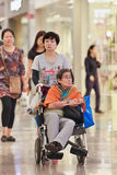 Женщина с неработающей матерью в кресло-каталке на торговом центре Livat, Пекине, Китае Стоковые Фотографии RF