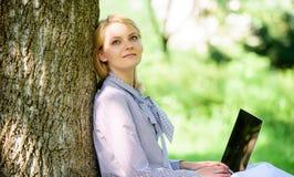 Женщина с ноутбука работы деревом outdoors постным Минута для ослабляет Работа девушки с ноутбуком в парке сидеть на траве Образо стоковые изображения