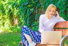 Женщина с ноутбуком работает на открытом воздухе зеленая предпосылка природы Удаленные работы просматривают верхние независимые у стоковое изображение