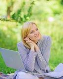 Женщина с ноутбуком сидит на луге травы половика Онлайн независимая концепция карьеры Приятное занятие Начало проводника стоковое изображение